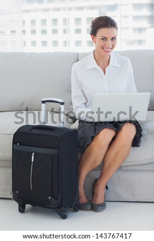 Businesswoman sitting on the couch with laptop with suitcase - stock photo