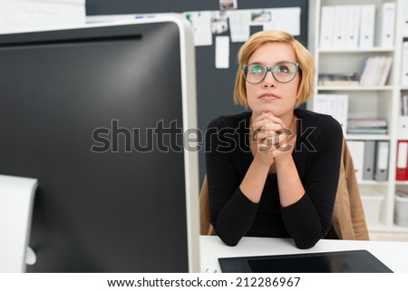 Businesswoman sitting thinking and planning at her desk staring up into the air with her chin resting on her clasped hands - stock photo