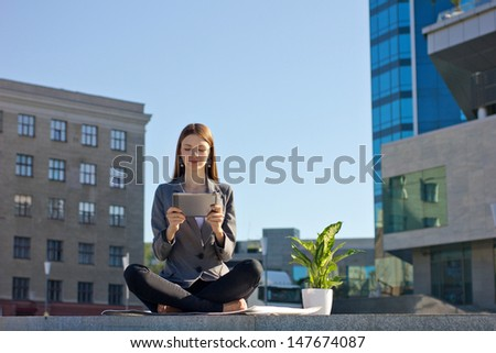 businesswoman sitting with legs crossed outdoor, holding laptop, near - flower in pot, on building and sky background - stock photo