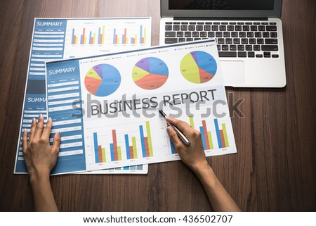 businesswoman sitting working at her desk in the office checking and analysing a report. Accounting - stock photo