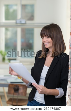 Businesswoman smiling as she reads a handheld document while leaning against a wall in the office - stock photo