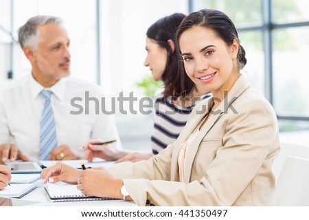 Businesswoman smiling at camera while colleagues discussing in the background - stock photo