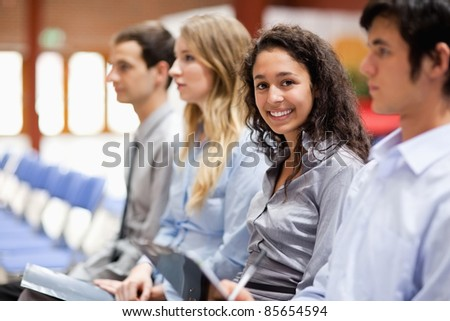 Businesswoman smiling at the camera during a presentation - stock photo