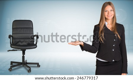 Businesswoman smiling showing something or copyspase for product or sign text. Office chair beside. Hi-tech graphs with various data as backdrop - stock photo