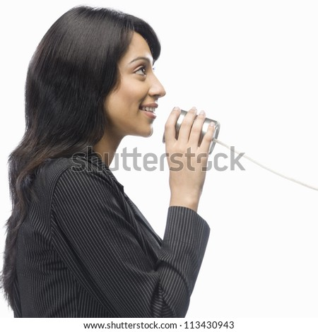 Businesswoman speaking in a tin can phone - stock photo