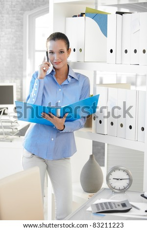 Businesswoman speaking on cellphone, holding folder, smiling confidently at camera.? - stock photo