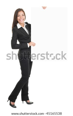 Businesswoman standing and holding a white empty billboard or signboard in full length. Beautiful mixed race chinese / caucasian woman isolated on white background. - stock photo