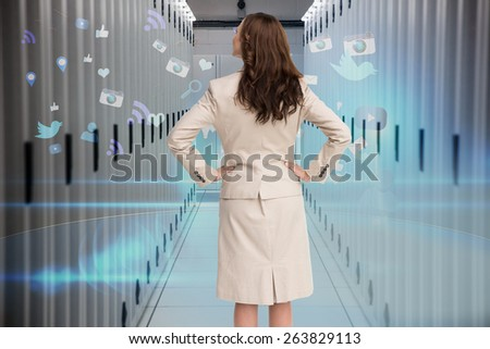 Businesswoman standing back to camera against data center - stock photo