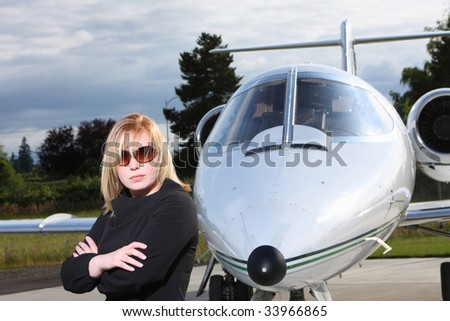 Businesswoman standing by corporate jet - stock photo