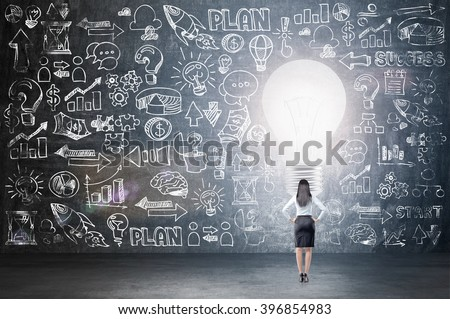 Businesswoman standing in front of blackboard with many business icons, big light bulb in front. Back view. Concept of having new idea. - stock photo
