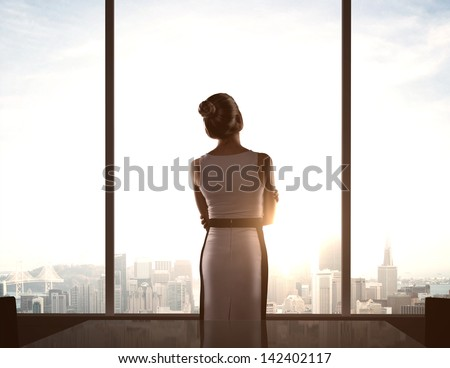 businesswoman standing in office and looking in city - stock photo