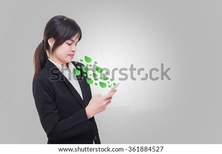 Businesswoman standing in the way businesses handle phone to communicate, Leaf out of the mobile media innovation to coexist with nature. - stock photo