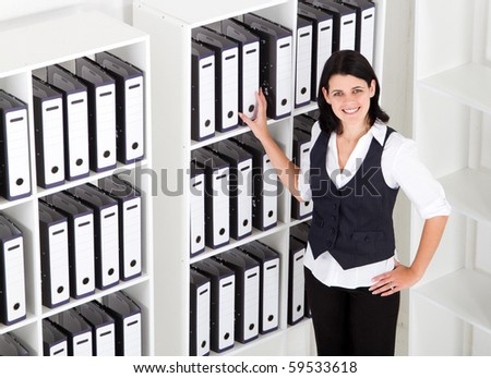 businesswoman standing next to office files - stock photo