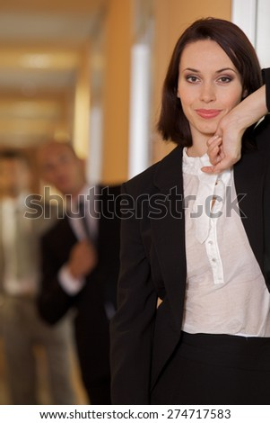 Businesswoman standing on door while businessman standing in background - stock photo