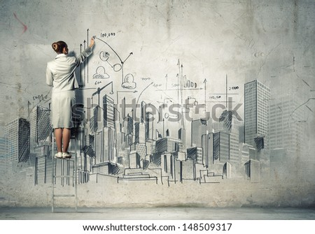 Businesswoman standing on ladder and drawing sketch on wall - stock photo