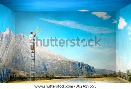 Businesswoman standing on ladder drawing sun on wall - stock photo