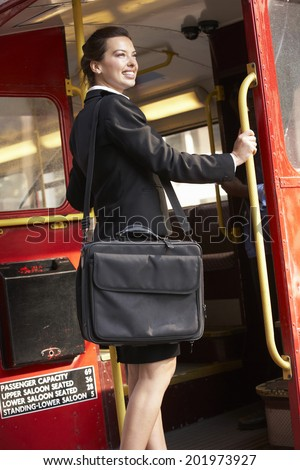 Businesswoman standing on Routemaster bus platform - stock photo