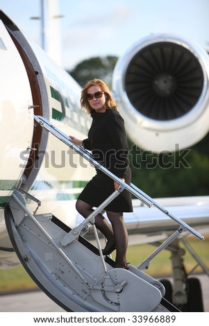 Businesswoman standing on stairs to private jet - stock photo