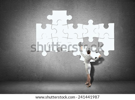 Businesswoman standing with back and connecting puzzles - stock photo