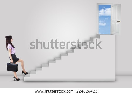 Businesswoman stepping up to the door on the sky with an arrow direction to the door - stock photo