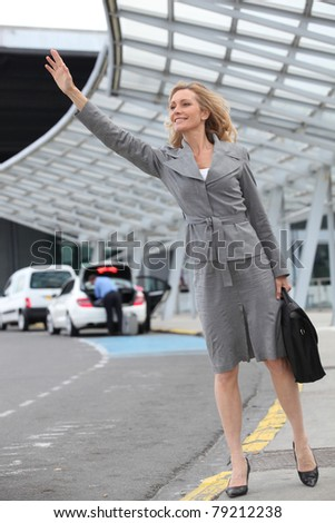 Businesswoman stopping taxi - stock photo