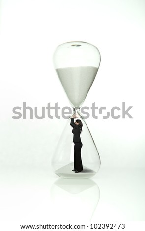 Businesswoman stops time from the hourglass - stock photo