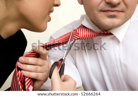 Businesswoman stressed with scissors trying to cut tie of her boss - stock photo