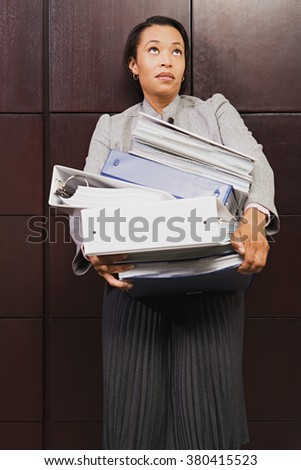 Businesswoman struggling with heavy files - stock photo