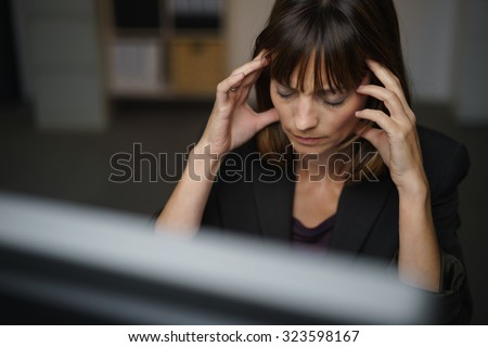 Businesswoman suffering from a headache or migraine holding her hands to her throbbing temples as she works late in the office to a deadline - stock photo