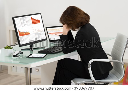Businesswoman Suffering From Headache Pain While Working In Office - stock photo