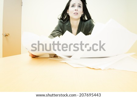 Businesswoman swamped with paperwork - stock photo
