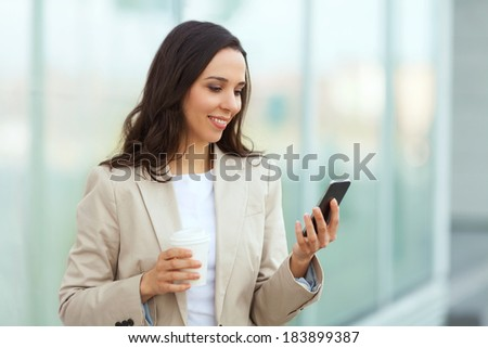 Businesswoman taking a coffee break and using smartphone. - stock photo