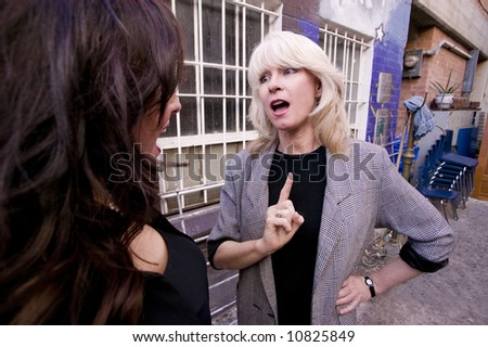Businesswoman talking and gesturing in an alley - stock photo