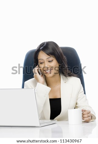 Businesswoman talking on a mobile phone and using a laptop - stock photo