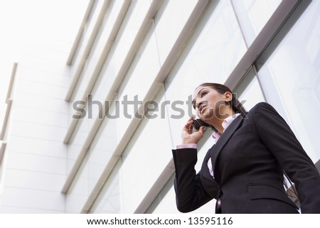 Businesswoman talking on cell phone outside modern office - stock photo