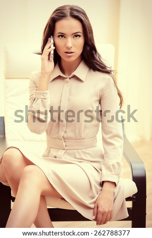 Businesswoman talking on her cellphone in the office. - stock photo