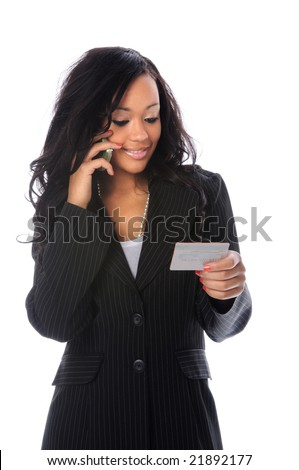 Businesswoman talking on the cell phone and holding a credit card - stock photo