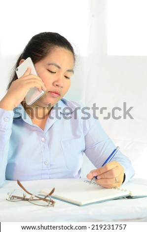businesswoman talking on the phone and taking notes - stock photo