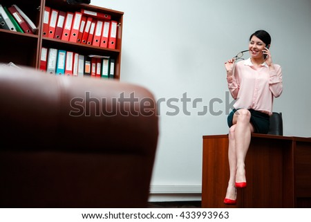 Businesswoman talking on the phone in office. - stock photo