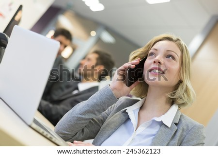 Businesswoman talking on the smart phone in modern office - stock photo