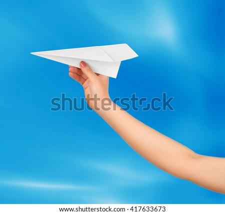 Businesswoman throwing white paper plane - stock photo