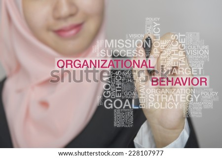 Businesswoman touch screen concept with Organizational Behavior wordcloud - stock photo