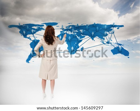 Businesswoman touching at a world map with blue sky on the background - stock photo