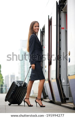 Businesswoman traveling and entering train with suitcase - stock photo