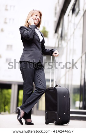 Businesswoman traveling.Front view of a traveler woman walking and using a smart phone in an airport. - stock photo