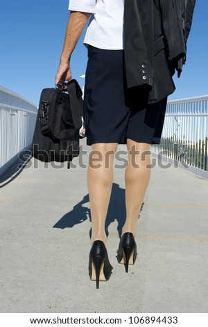 Businesswoman traveling with laptop, wearing white blouse, dark skirt and high heel shoes, isolated with blue sky as background and copy space. - stock photo