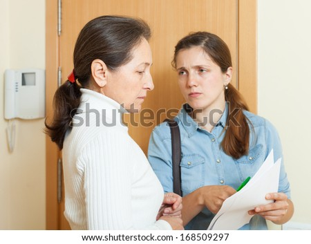 businesswoman trying to collect arrearages from mature woman at home  - stock photo