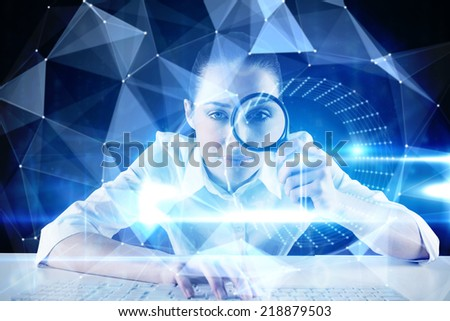 Businesswoman typing and looking through magnifying glass against blue technology design with tunnel - stock photo