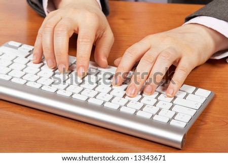Businesswoman typing on computer keyboard. Shallow depth of field - stock photo