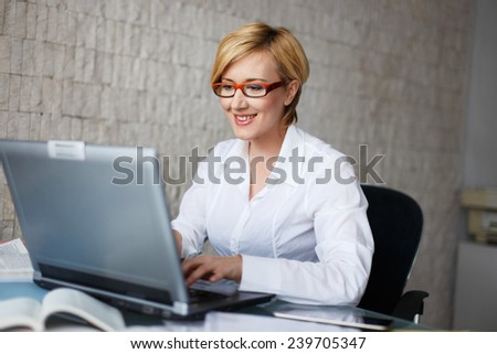 Businesswoman typing on laptop in office - stock photo